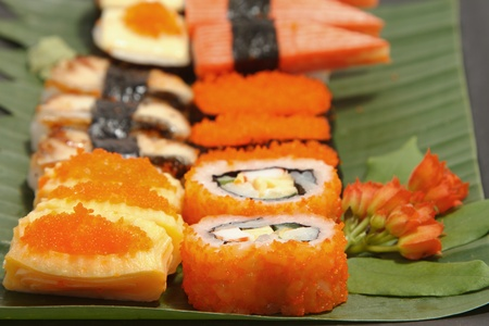 fine fish: Assorted japanese sushi on a black plate on white background Stock Photo