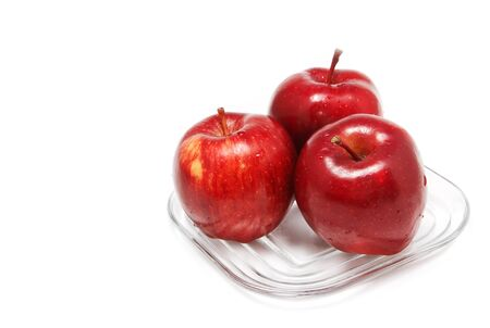 three red apples in dish on white background photo