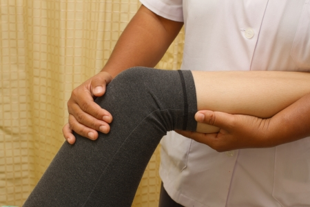 a physio therapist trying to test the knee and leg  Stock Photo