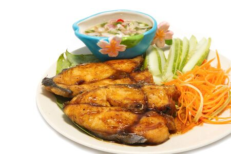 fired fish with fishsauce and spicy mango slad ,on white background photo