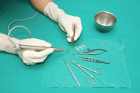 set of eye surgical instrument on sterile table with a hand of doctor grabbing a tool photo