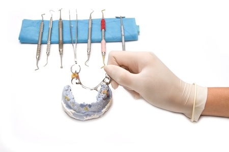 Dental prosthesis on gypsum model plaster with doctor hand graping photo
