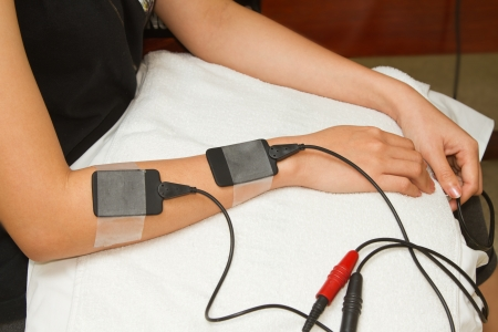 stimulator: Electrical stimulation forearm ,physical therapist helping woman with electrical stimulator for increase muscle strength and release pain