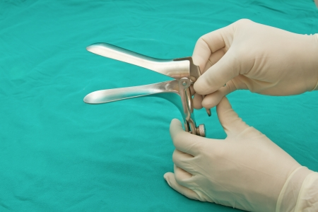 doctor s hand graping the Medical equipment ,Gynecologic Speculum photo