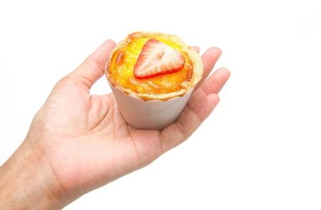 egg tart: Hand with egg tart on isolate