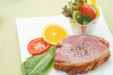 Smoked ham stack with fruit and vegetable salad on the white plate photo