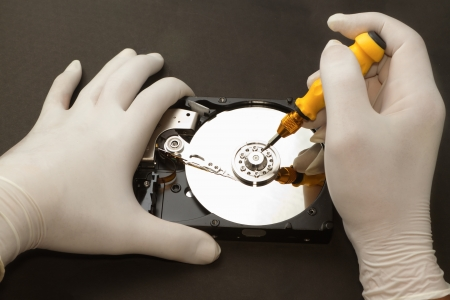 Hand with gloves repairs hard drive ,data recovery concept