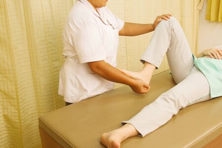 weakness: Physiotherapist treating quadriceps muscle,Rehabitation  for muscle weakness Stock Photo