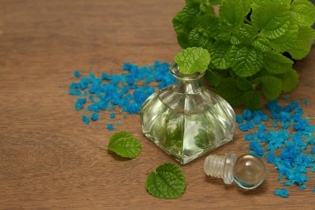 Essential aroma peppermint oil and  fresh mint  on wooden background photo