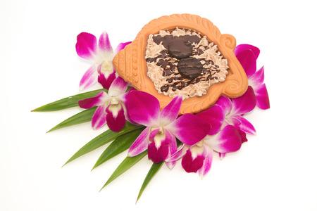 olla barro: Pastelitos de chocolate en una olla de barro con la orqu�dea tailand�s Foto de archivo
