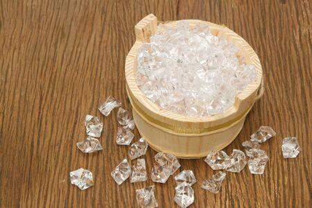 Cubos de hielo en cubo de madera