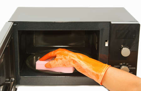 Hand with sponge cleaning microwave oven photo
