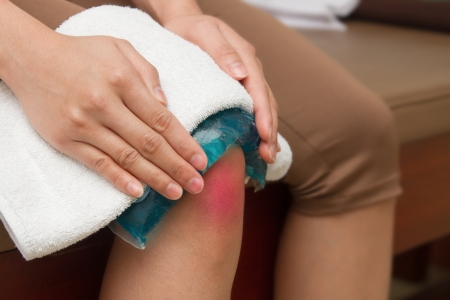 hurting: a woman applying cold pack on swollen hurting knee