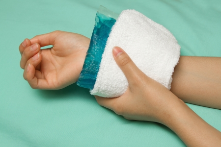 a woman applying cold pack on swollen hurting wrist Stock Photo
