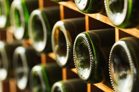 stacked of old wine bottles in the cellar Standard-Bild
