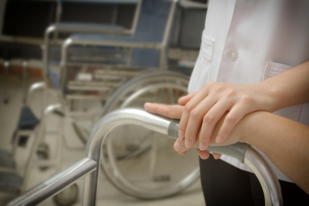 Doctor holding patient s hand in a walker photo