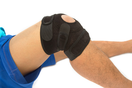 immobilize: man legs with one knee in a protective knee brace