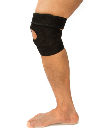 kneecap: man legs with one knee in a protective knee brace