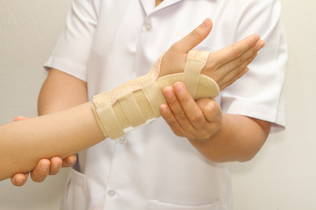 doctor putting wrist  brace on the patient's arm Standard-Bild