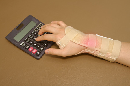 womans hand with wrist support  doing calculations on calculator photo