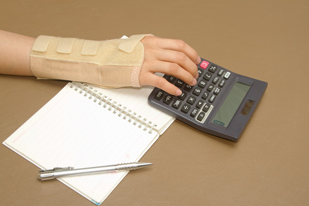 womans hand with carpal tunnel syndrome doing calculations on sheet of paper photo