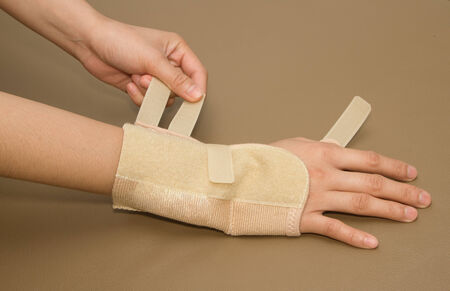 carpal tunnel syndrome: womans hand with carpal tunnel syndrome remove the wrist brace Stock Photo