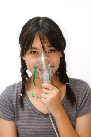 inhale: a cute asian  girl with a mask for inhaler
