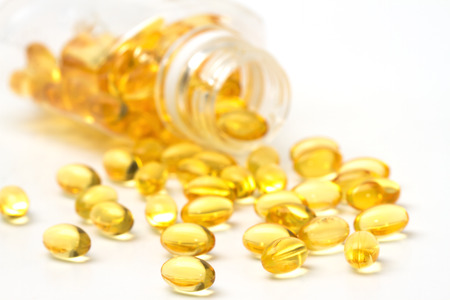 vitamin capsules with  E poured out of bottle photo