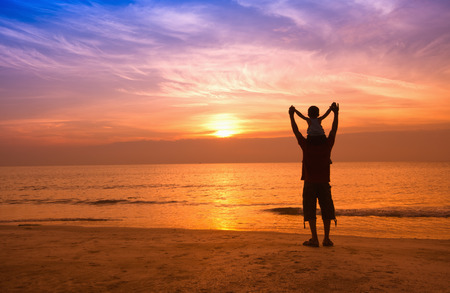day dream: silhouettes of father and son on sunrise sea background,family concept