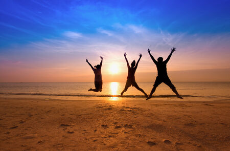 happy family concept: family jumping team on the beach on beautiful sunrise silhouette shot,happy family concept