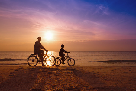 father and son at the beach on sunset,Biker family silhouette  photo