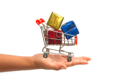 Hand holding shopping cart with gift boxes photo