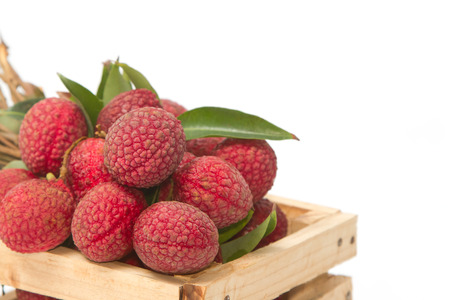 Fresh lychees with leaves in crate