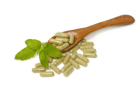 Kruidengeneesmiddel capsules inwooden lepel. Alternatieve geneeskunde concept.