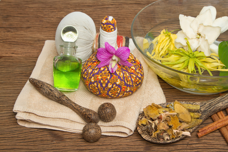 Thai spa massage setting with thai  herbal compress balls, essential oil bottle, towel,ylang-ylang flower