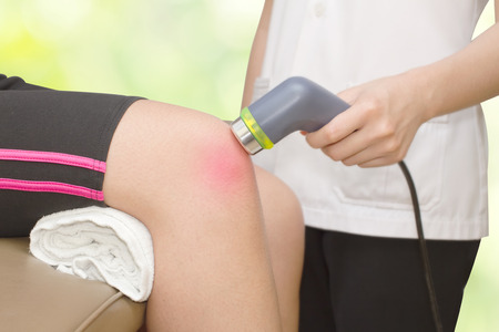Physical therapist using ultrasound probe on woman patient 's knee for release pain Foto de archivo