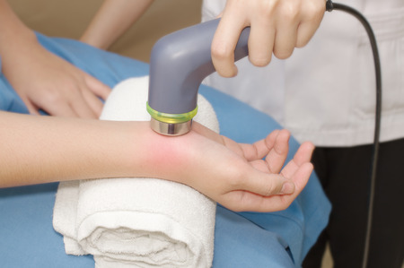 Physical therapist using ultrasound probe on woman patient s hand for release pain photo