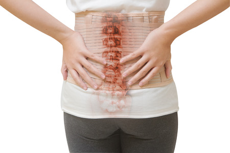 Woman in back pain from spinal injury wearing lumbar brace corset