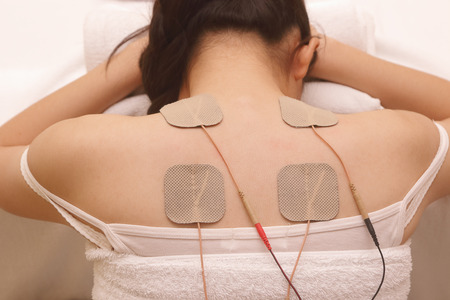 Asian woman is doing massage of electrical -stimulation ( TENs ) for the back Stock Photo