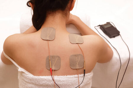 stimulation: Asian woman is doing massage of electrical -stimulation ( TENs ) for the back Stock Photo