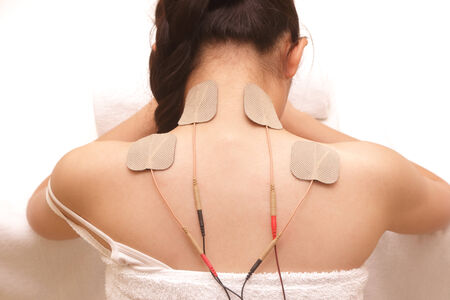 stimulator: Asian woman is doing massage of electrical -stimulation ( TENs ) for the back Stock Photo