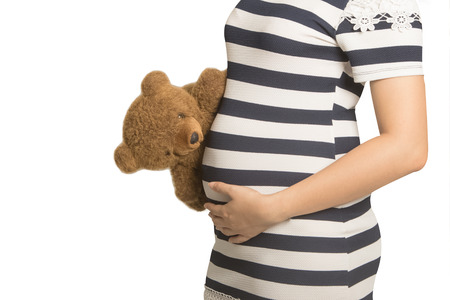 peaking: Close up on pregnant belly. Woman expecting a baby with a cute teddy bear peaking at her belly.
