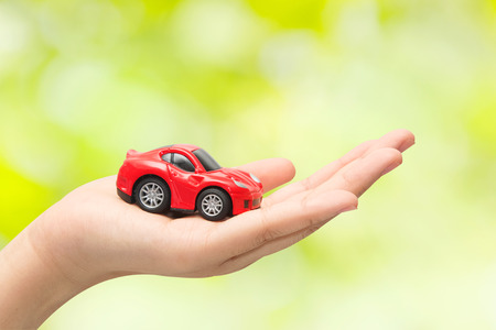 fully comprehensive: hand holding the model of car on green background. symbol photo for car purchase