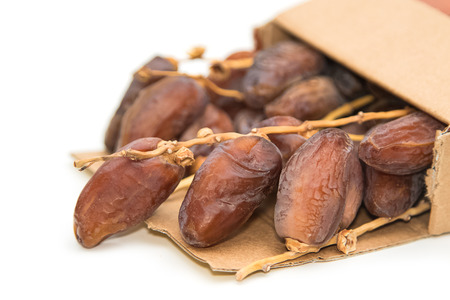 deglet: close up of dried dates in paper box  on white background