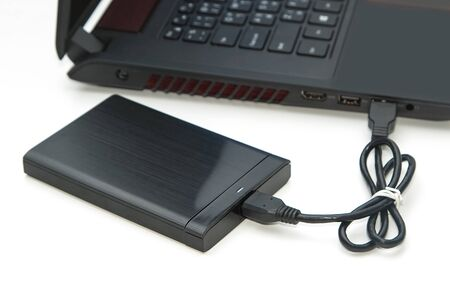 external: external hard disk connect to computer notebook on white. Stock Photo