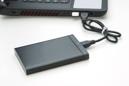 portable hard disk: external hard disk connect to computer notebook on white. Stock Photo