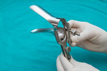 의사는 그의 손에 일회용 검경을 보유하고있다.