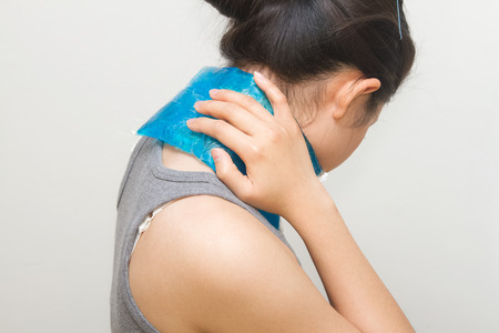 cold woman: woman putting gel pack on swollen neck