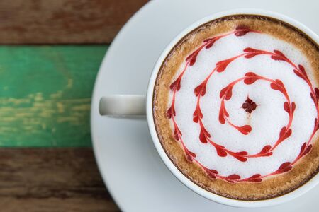 capuchino: Capuchino or latte coffee  in a white cup with heart shaped foam on wooden board