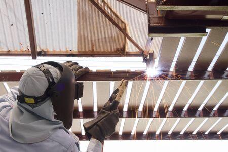 soldadura: Soldadura del trabajador industrial brida de la tubería de acero, una soldadura de chispa. Foto de archivo
